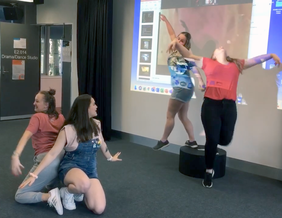 Four students in animated poses in a drama class in front of zoom projection